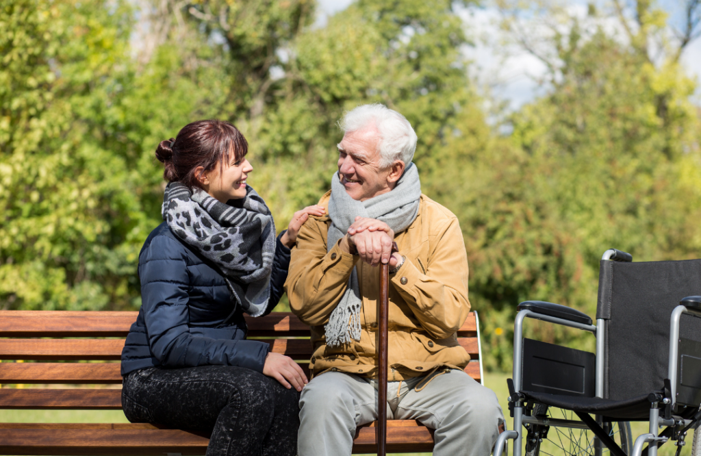 Image: Two people are sat on a bench in the park. It is a sunny day. The younger person is supporting the other person and they are both smiling and are happy to see each other.