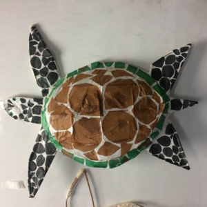 The picture shows a large lantern that has been made into the shape of a turtle. Different shaped circles have been cut out in black that covers the flippers, head and tail. Larger brown circles fill the shell and the rim of the shell is decorated with green squares and rectangles.